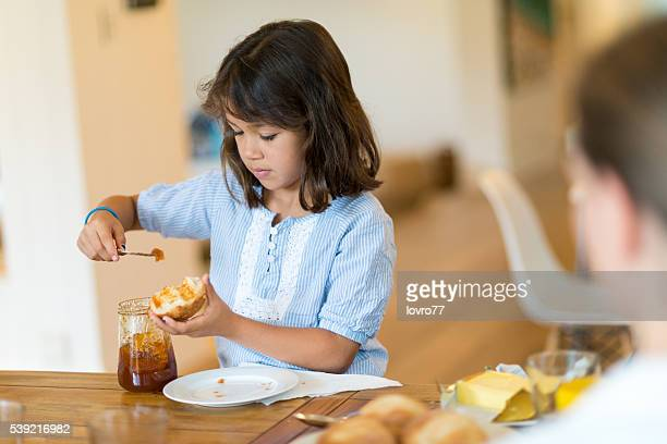 Girl putting marmalade on the bread