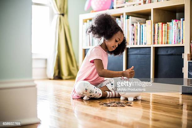 girl putting money in piggybank