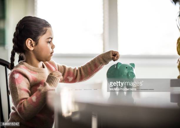 girl (7 yrs) putting money in piggybank - piggy bank stock photos and pictures
