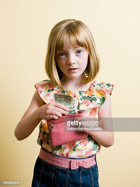 girl putting money into her purse