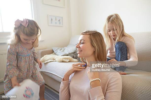 Girl putting necklace onto mother in living room