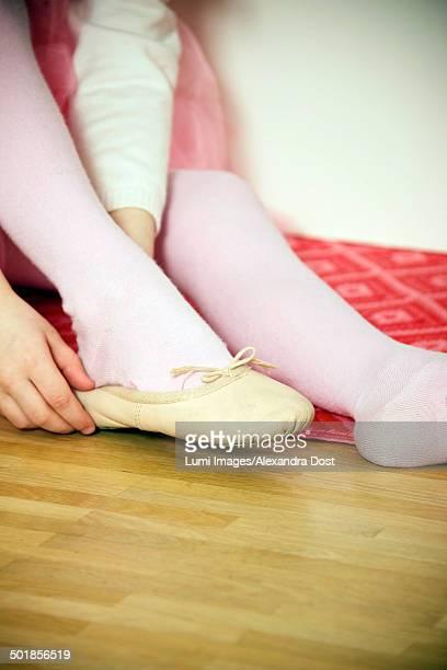 Girl putting on ballet shoe