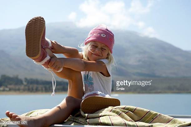 Girl (6-8) putting on boots near lake