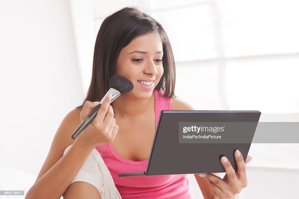 Girl putting on make-up : Stock Photo
