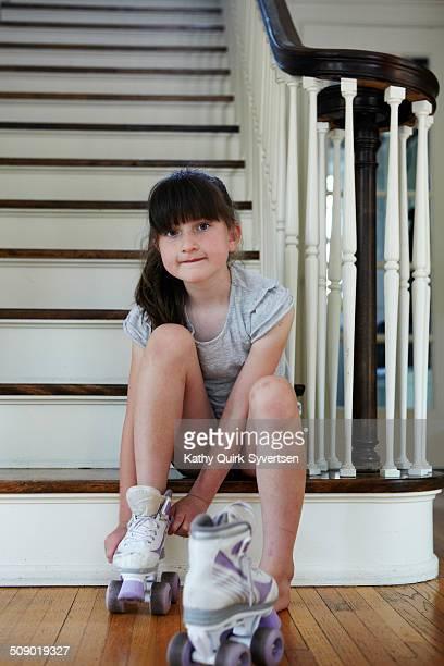 Girl putting on roller skates, foyer steps inside