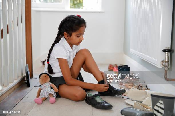 girl putting on shoes at home - school girl shoes stock pictures, royalty-free photos & images