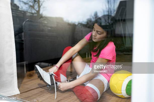 girl putting on soccer shoes in front of living room window - traje de fútbol fotografías e imágenes de stock
