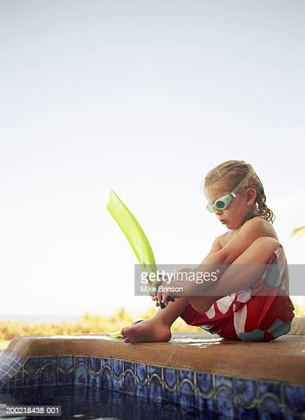 Girl (4-6) putting on swimming fins near pool