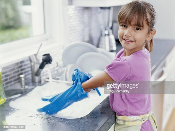 girl (6-8) putting on washing up gloves at sink, smiling, portrait - kids with cleaning rubber gloves stock pictures, royalty-free photos & images