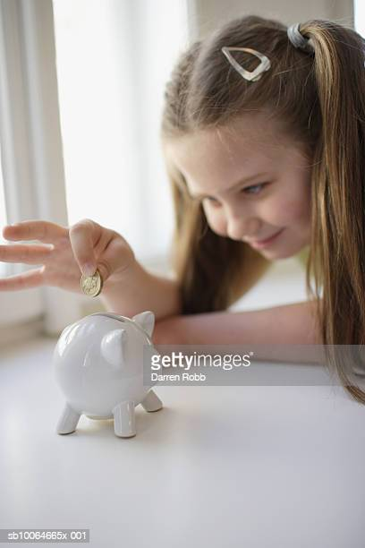 Girl (10-11) putting one pound coin into piggy bank, smiling, (focus on foreground)