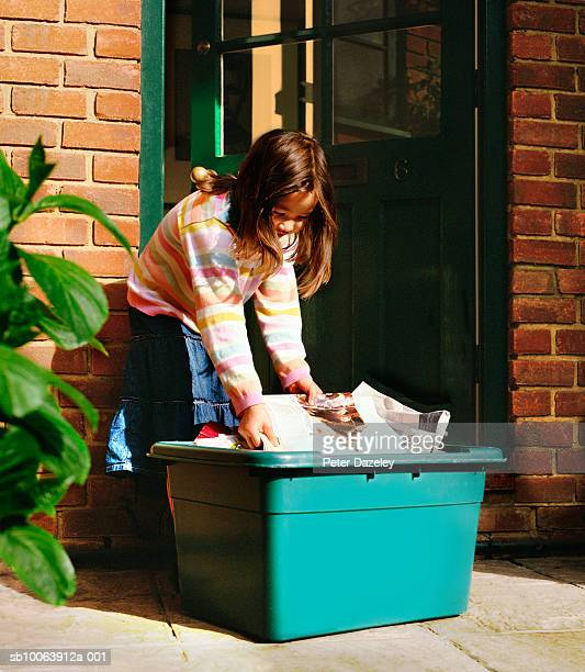 Girl (6-7) putting out newspapers in recycling box