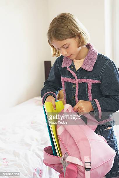 Girl putting school books into backpack