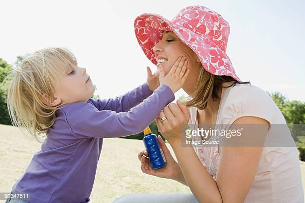 Girl putting suncream on mother