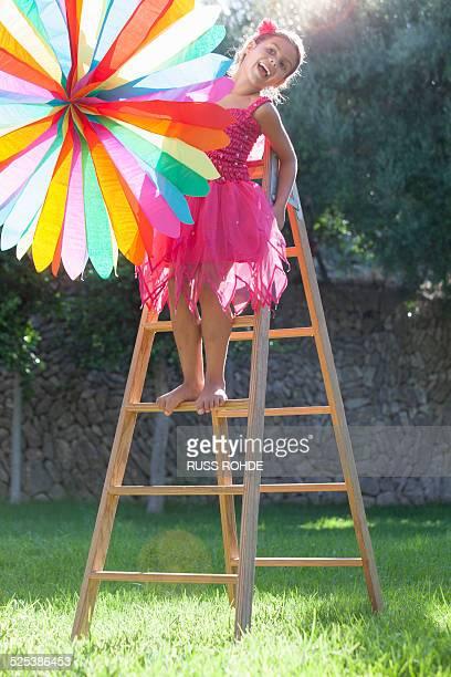 Girl putting up decoration in garden