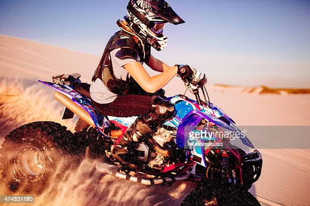 Girl quad racer in protective gear racing over sand dunes