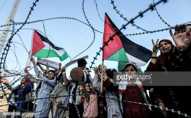 Girl raises a Palestinian flag as another Palestinian boy holds a wooden key symbolising the return, as they stand with others before the barbed-wire...