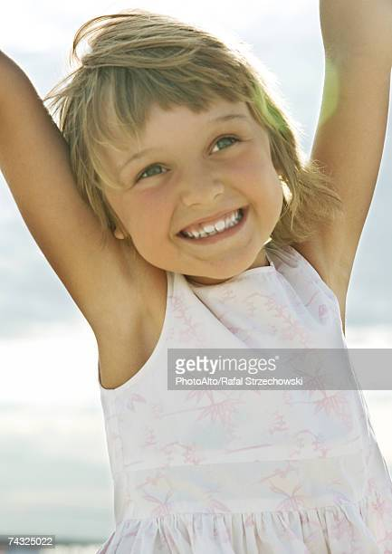 Girl raising arms, smiling, portrait