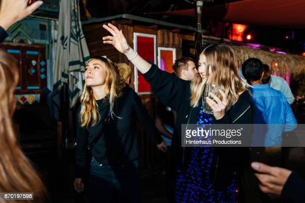girl raising hand in the air while dancing at nightclub with friends - party stock-fotos und bilder