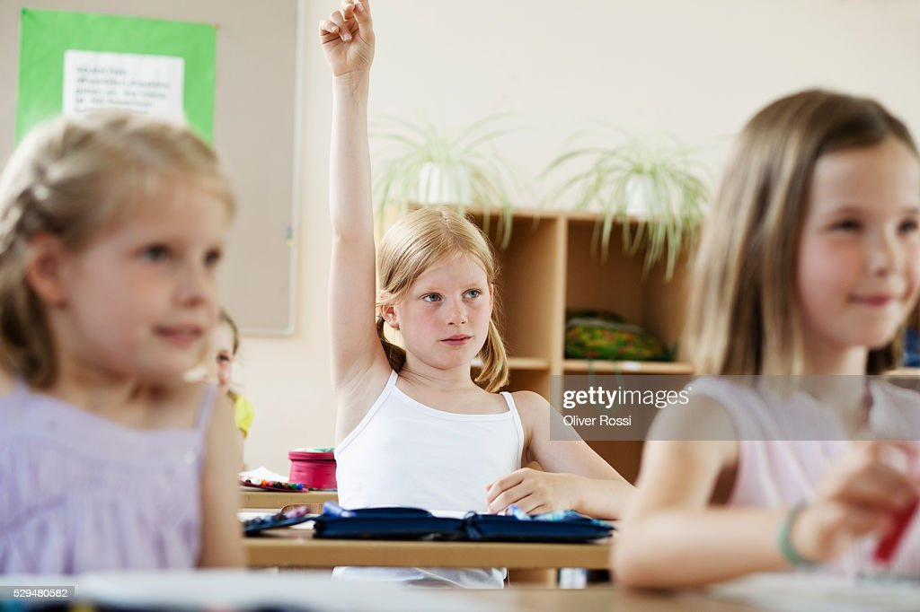 Girl raising hands in classroom : Stock Photo
