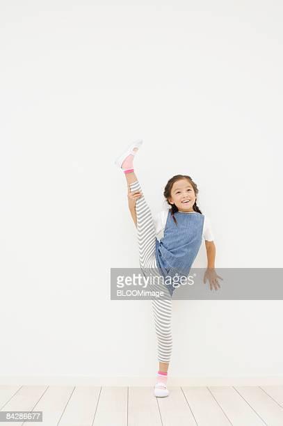 Girl raising leg over head