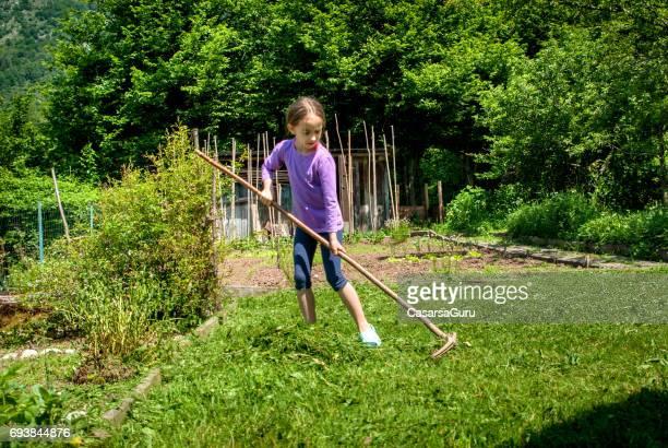 Girl Raking  Cutting Grass In The Garden