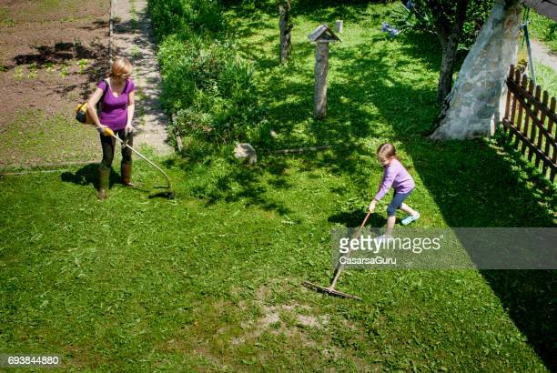 Girl  Raking Grass While Mother Cutting Grass With Weed Trimmer