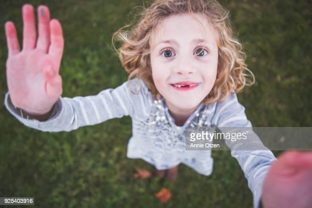 Girl reaches upward toward the camera