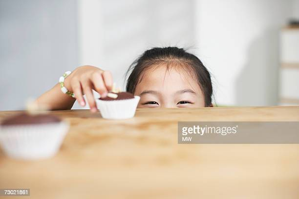 'Girl (5-7) reaching cupcake on counter, high section'