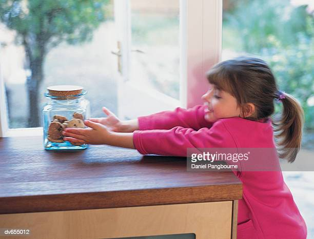 Girl Reaching for a Jar of Cookies