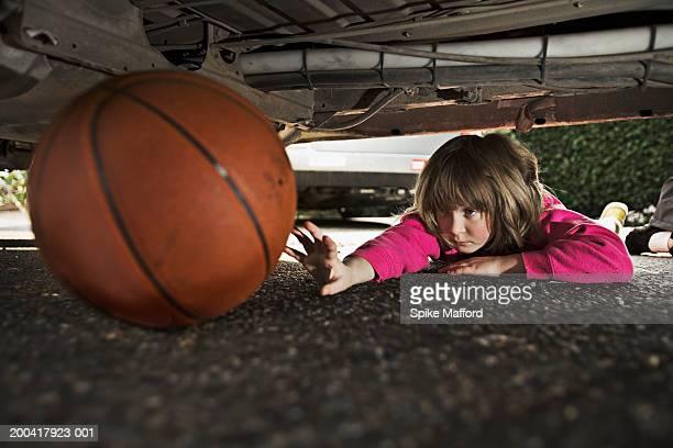 Girl (6-8) reaching for basketball under car