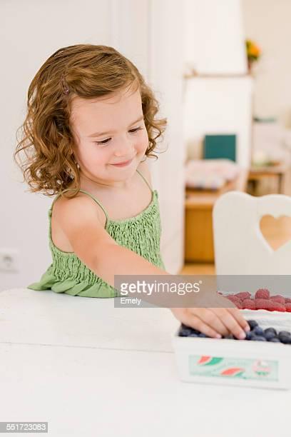 Girl Reaching for Blueberries