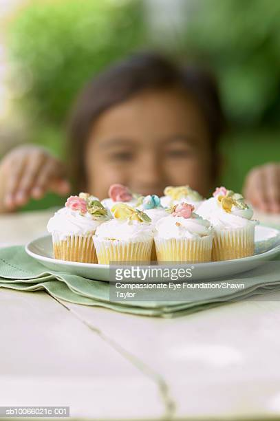Girl (6-7) reaching for cupcakes on table (differential focus)