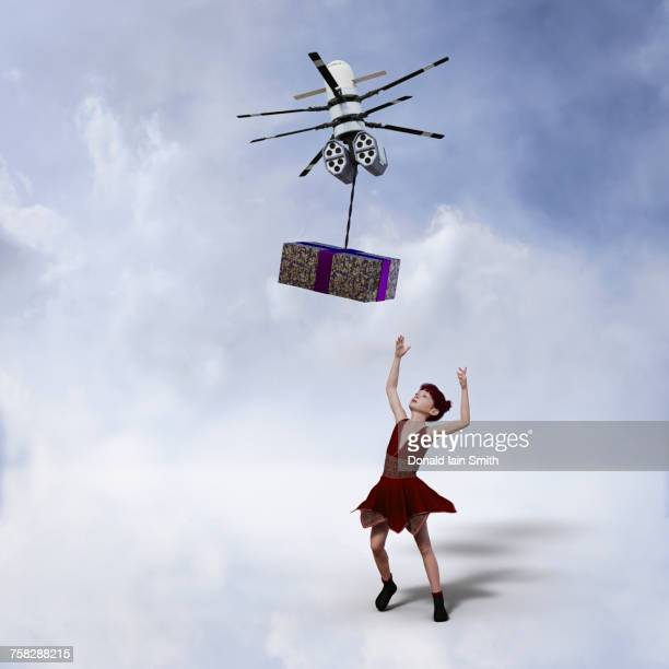 Girl reaching for gift delivered by drone