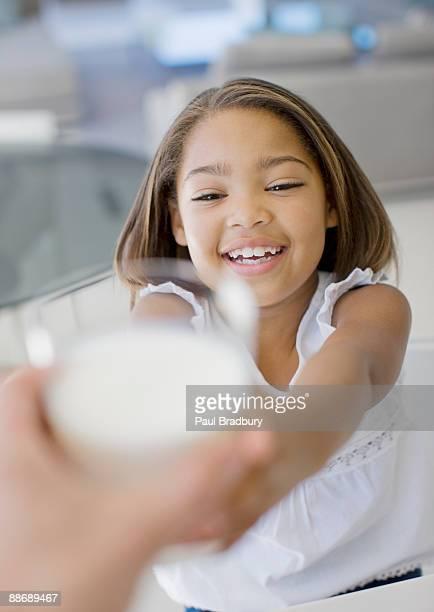 Girl reaching for glass of milk