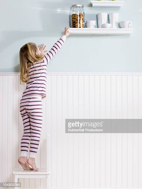 girl reaching for jar of cookies - reaching stock pictures, royalty-free photos & images