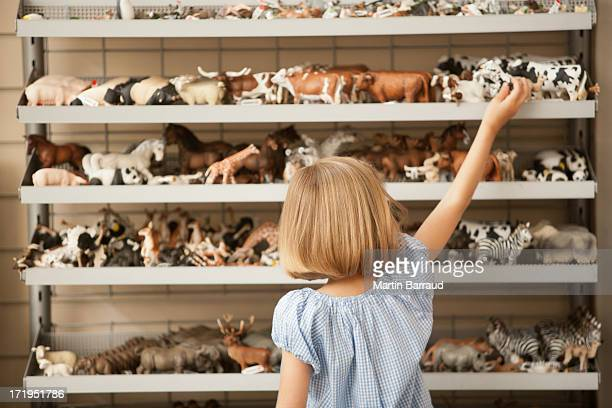 girl reaching for plastic cow in toy store - animal representation stock pictures, royalty-free photos & images