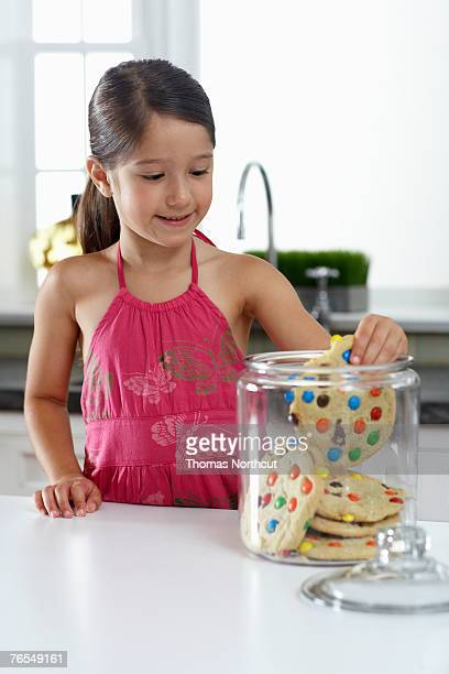 Girl (4-6) reaching into cookie jar on kitchen counter