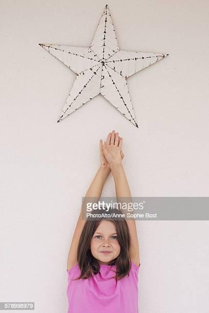 Girl reaching toward star shape hanging above her head, portrait