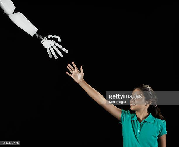 A girl reaching up to touch a robotic hand.
