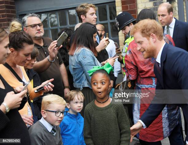 A girl reacts after posing for a picture with Prince Harry during a visit to the newly established Royal Foundation Support4Grenfell community hub on...