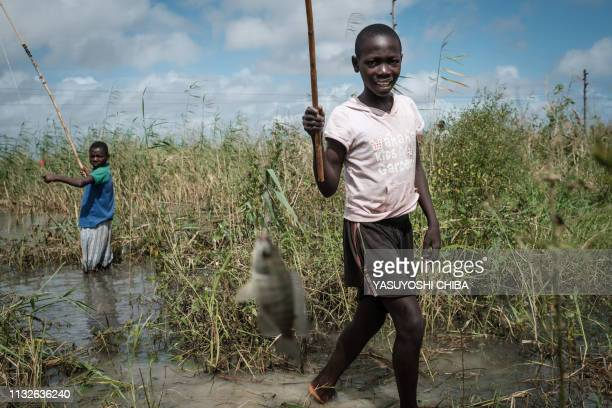 A girl reacts after she caught a fish in a flooded area hit by the Cyclone Idai near Tica Mozambique on March 24 2019 Cyclone Idai smashed into...