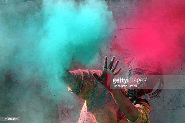 A girl reacts as others throw colored powder on her while celebrating Holi on March 7 2012 in Jammu India Holi the festival of colors celebrates the...