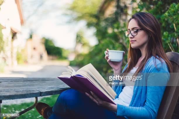 menina lendo um livro no quintal - patio de colegio - fotografias e filmes do acervo