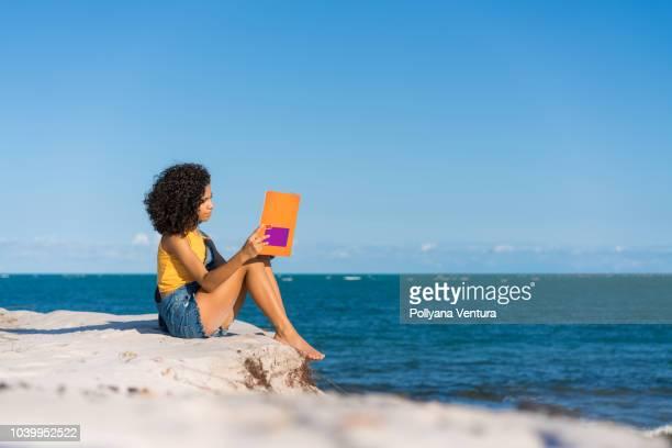 niña leyendo un libro en la playa - pantalón naranja fotografías e imágenes de stock