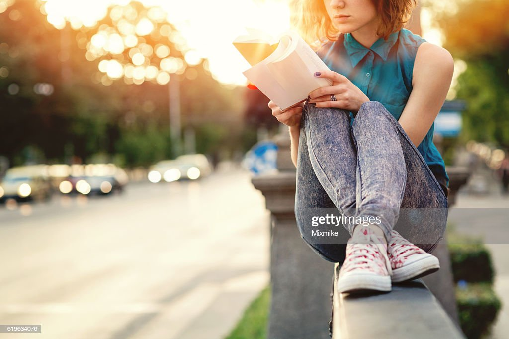 Girl reading a book in the city : Stock Photo