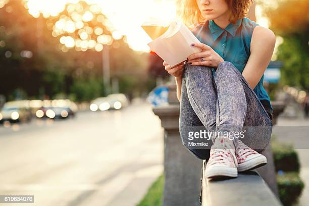 Girl reading a book in the city