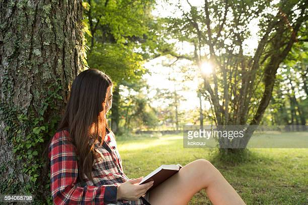 Girl reading a book leaning on a tree.