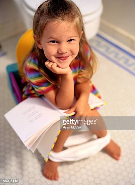 Girl Reading a Book on a Potty Chair