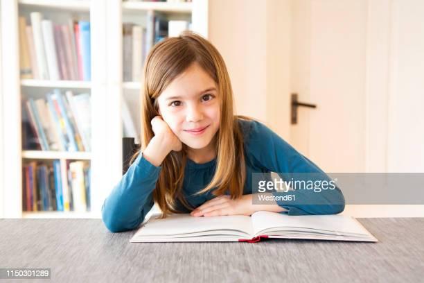 girl reading a book - schulbuch stock-fotos und bilder