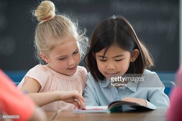 Mädchen beim Buchlesen zusammen